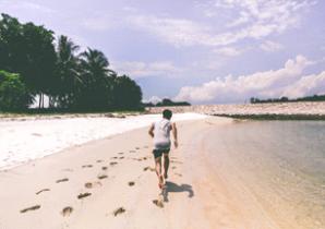 Man running on a beach on a sunny day