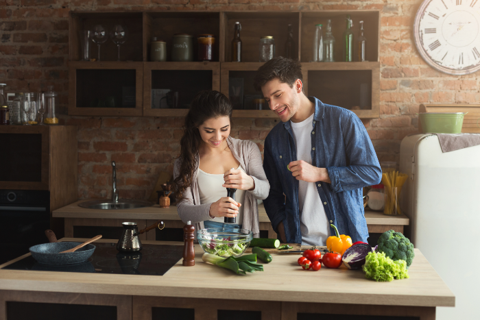 Happy couple (man and woman) cooking vegetables in their kitchen.