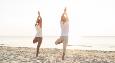 Man and woman doing yoga on the beach