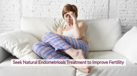 Woman sitting on couch in pain from endometriosis symptoms