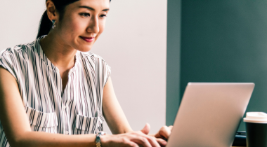 Woman sitting on laptop smiling